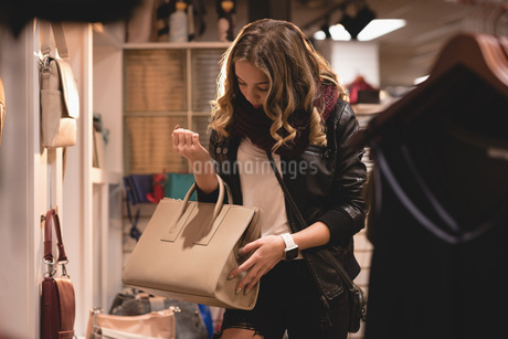 Beautiful woman checking out handbag from displayの写真素材 [FYI02242429]