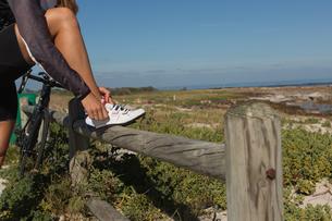Female biker wearing her shoe laceの写真素材 [FYI02242451]