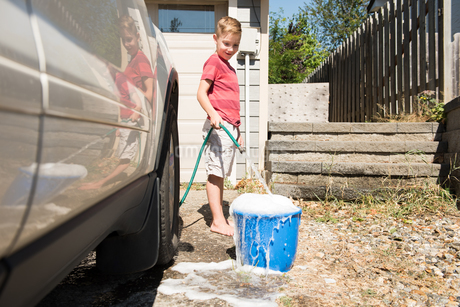 Boy filling water in bucketの写真素材 [FYI02242459]