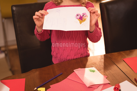 Girl showing valentine card at homeの写真素材 [FYI02242480]