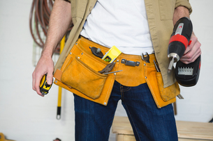 Male carpenter with tool belt in workshopの写真素材 [FYI02242489]