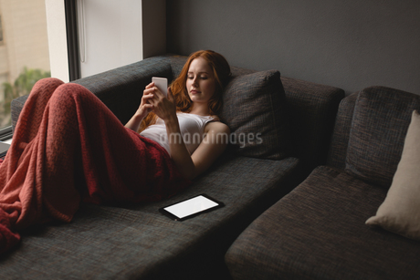 Woman using mobile phone at homeの写真素材 [FYI02242491]