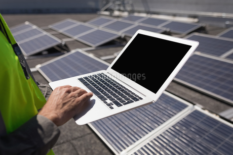Male worker using laptop at solar stationの写真素材 [FYI02242495]