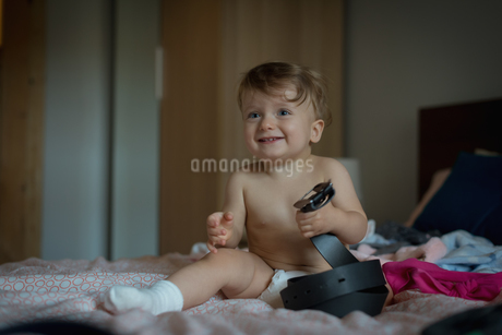 Baby boy playing on bedの写真素材 [FYI02242518]