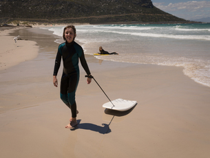 Portrait of teenage girl in wetsuit walking with surfboardの写真素材 [FYI02242532]