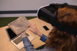 Woman touching wooden slab while using virtual reality headsetの写真素材 [FYI02242538]