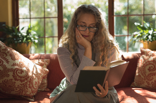 Mature woman sitting on sofa while reading novelの写真素材 [FYI02242559]