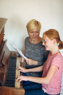 Mother assisting daughter in playing piano at homeの写真素材 [FYI02242580]