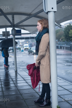 Young woman holding an umbrella standing at bus stopの写真素材 [FYI02242627]