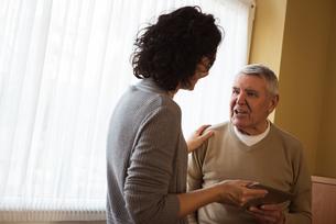 Caretaker showing digital tablet to senior womanの写真素材 [FYI02242629]