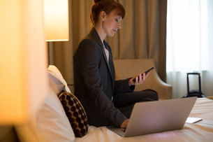 Businesswoman using mobile phone while working on laptopの写真素材 [FYI02242659]