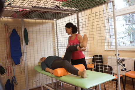 Female physiotherapist giving knee massage to senior patientの写真素材 [FYI02242672]