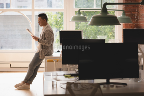 Male executive sitting on table reading documentsの写真素材 [FYI02242696]