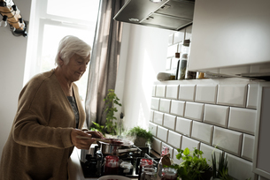 Senior woman cooking food in the kitchenの写真素材 [FYI02242710]