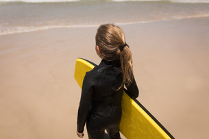 Girl standing with surfboard on beachの写真素材 [FYI02242712]