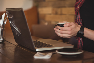 Mid section of man using laptop while having coffeeの写真素材 [FYI02242736]