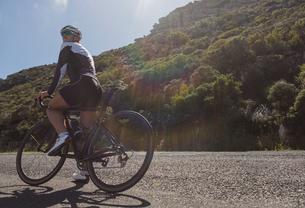 Female biker taking a break on roadの写真素材 [FYI02242759]