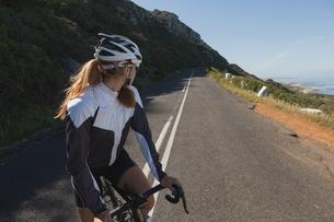 Female biker looking back while riding mountain bikeの写真素材 [FYI02242764]