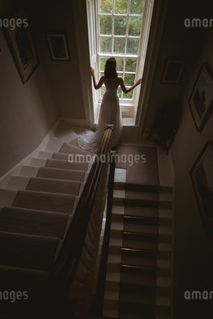 Bride standing at the window at homeの写真素材 [FYI02242793]