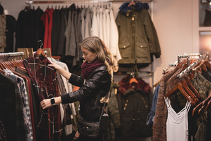 Beautiful woman selecting clothes from rackの写真素材 [FYI02242805]