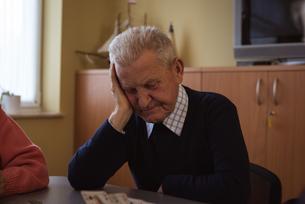 Tense senior man playing cardの写真素材 [FYI02242819]