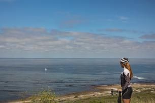 Female biker with mountain bike looking at seaの写真素材 [FYI02242831]