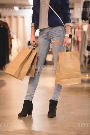 Low section of woman standing with shopping bagsの写真素材 [FYI02242835]