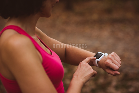 Woman using smart watch in forestの写真素材 [FYI02242853]