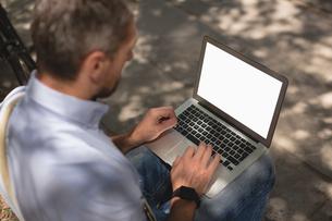 Man using laptop in parkの写真素材 [FYI02242855]