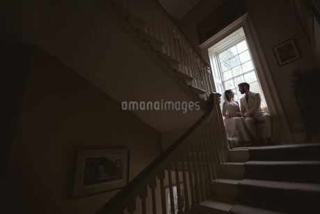 Bride and groom sitting on the window sillの写真素材 [FYI02242863]