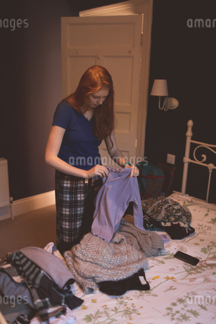Woman folding clothes in bedroomの写真素材 [FYI02242869]