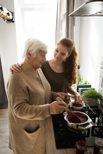 Grandmother and grand daughter cooking in the kitchenの写真素材 [FYI02242897]