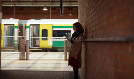 Woman using mobile phone at railway stationの写真素材 [FYI02242944]