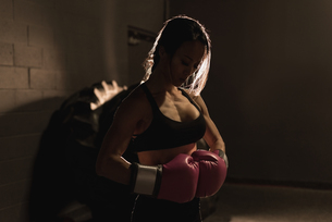 Determined woman standing with boxing glovesの写真素材 [FYI02242947]