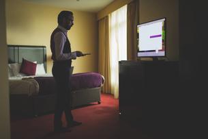 Businessman watching tv in roomの写真素材 [FYI02242954]