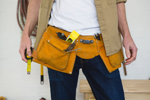 Male carpenter with tool belt in workshopの写真素材 [FYI02242965]