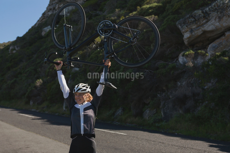 Excited female biker carrying mountain bikeの写真素材 [FYI02242969]