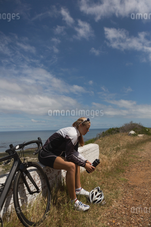 Female biker with water bottle sitting on rock benchの写真素材 [FYI02242970]