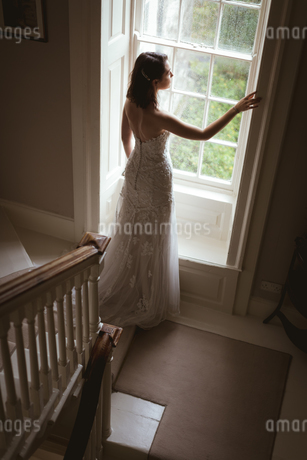Bride looking out of the window at homeの写真素材 [FYI02243006]