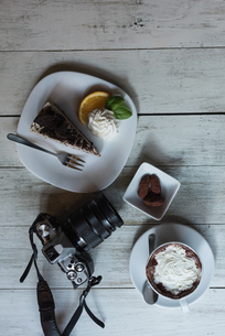 Camera and delicious sweet food on wooden tableの写真素材 [FYI02243022]