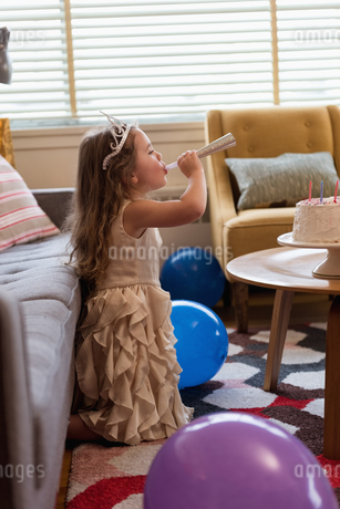 Cute girl blowing a party horn in living roomの写真素材 [FYI02243023]