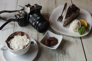 Camera and delicious sweet food on wooden tableの写真素材 [FYI02243028]