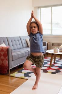 Little girl performing yoga in living roomの写真素材 [FYI02243032]