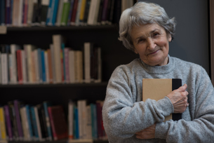 Senior woman holding a book in libraryの写真素材 [FYI02243038]