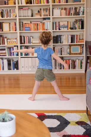 Little girl performing stretching exercise in living room at homeの写真素材 [FYI02243042]