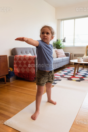 Little girl performing stretching exercise in living roomの写真素材 [FYI02243061]