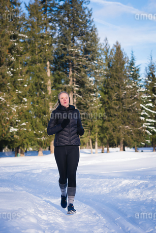 Athletic woman jogging on snowy landscapeの写真素材 [FYI02243075]