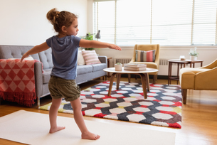 Little girl performing stretching exercise in living roomの写真素材 [FYI02243099]