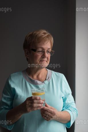 Senior woman having lemon juice at homeの写真素材 [FYI02243112]