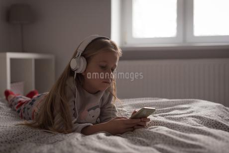Girl listening music on mobile phone with headphones in bedroomの写真素材 [FYI02243119]